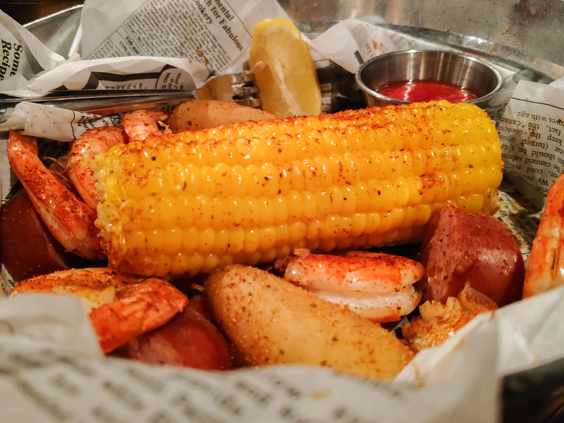 shrimp boil with sausage corn potatoes on dinner table