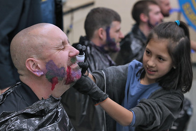 Josephine Reyes (right) sprays hair dye on the beard of Mike Matunas a member of the Spring Lake Heights Police department took part in the Spring Lake Heights Elementary School's No Shave November fund raiser. On Thursday December 6, 2018 the two winning 4th grade classes got to dye the beards of four police officers. (MARK R. SULLIVAN /THE COAST STAR)