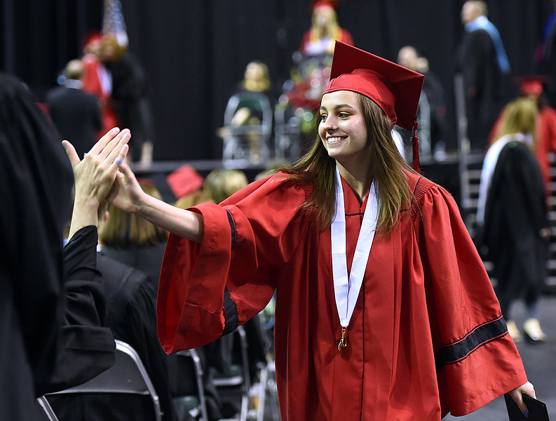 Loveland High School graduate Erica Johnson high-fives a teacher during her graduation ceremony Saturday, May 26, 2018, at the Budweiser Events Center at The Ranch in Loveland.   (Photo by Jenny Sparks/Loveland Reporter-Herald)