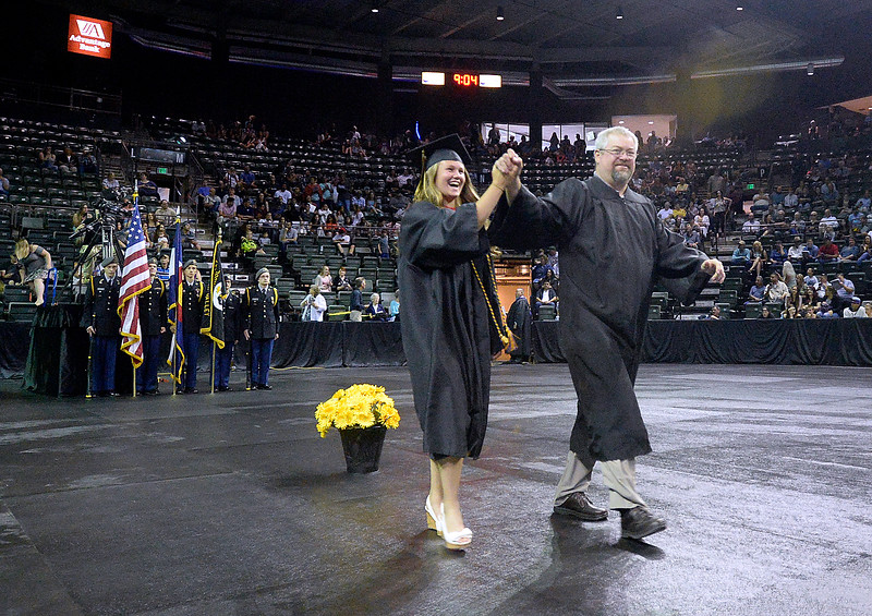 Thompson Valley High School Sydney Brian high-fives teacher Mike Burkett as they enter the arena for her graduation ceremony Saturday, May 26, 2018, at the Budweiser Events Center at The Ranch in Loveland.   (Photo by Jenny Sparks/Loveland Reporter-Herald)