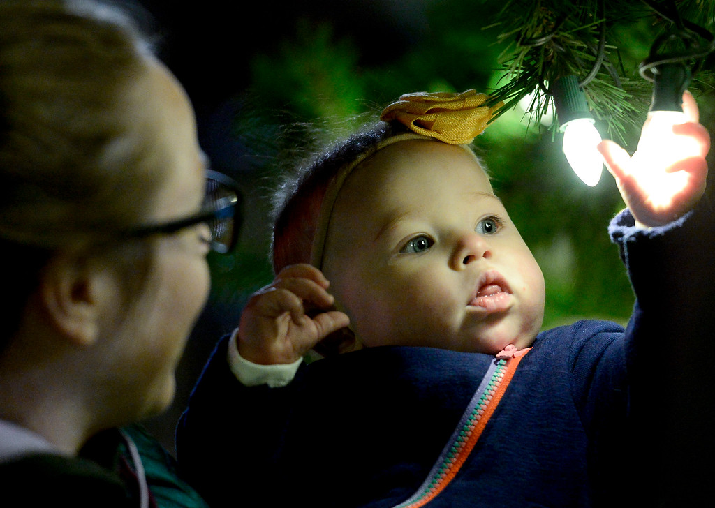 . LONGMONT, CO - NOVEMBER 23:Lauren Cely helps 8-month-old Olive Cely, both of Longmont, check out the lights during the tree lighting at the 6th Avenue Plaza in Longmont on Nov. 23, 2018. This year the tree lighting ceremony features LMNO Puppets, caroling, crafts, food, goodie bags and an appearance by Santa. (Photo by Matthew Jonas/Staff Photographer)