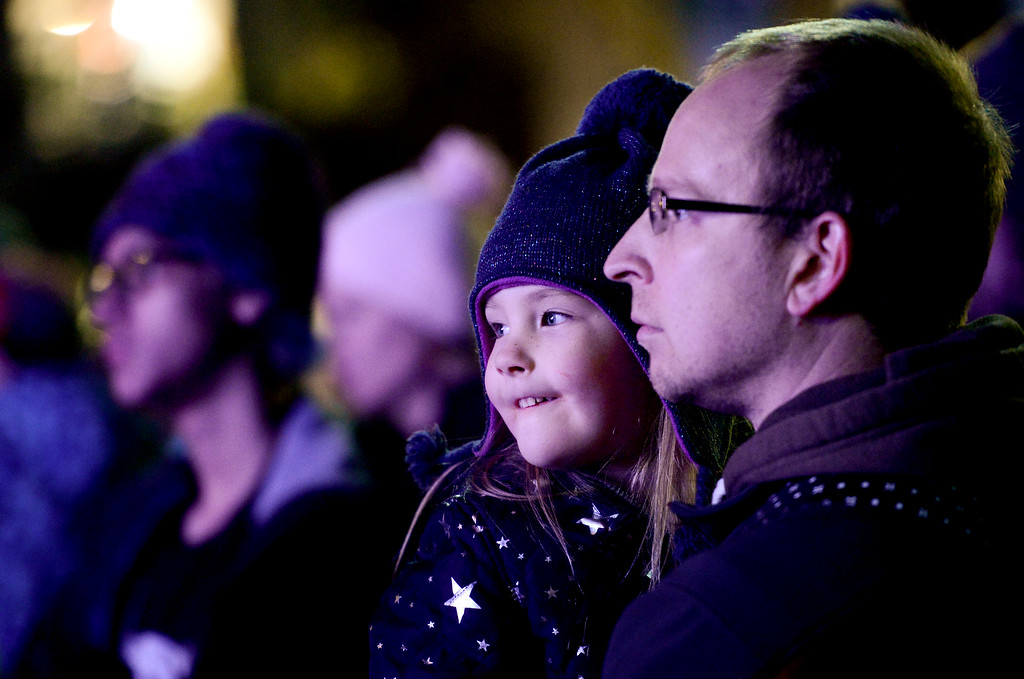 . LONGMONT, CO - NOVEMBER 23:From Right: Matt Abel and Molly Abel, 4, both of Longmont, watch the LMNO Puppets show during the tree lighting at the 6th Avenue Plaza in Longmont on Nov. 23, 2018. This year the tree lighting ceremony features LMNO Puppets, caroling, crafts, food, goodie bags and an appearance by Santa. (Photo by Matthew Jonas/Staff Photographer)
