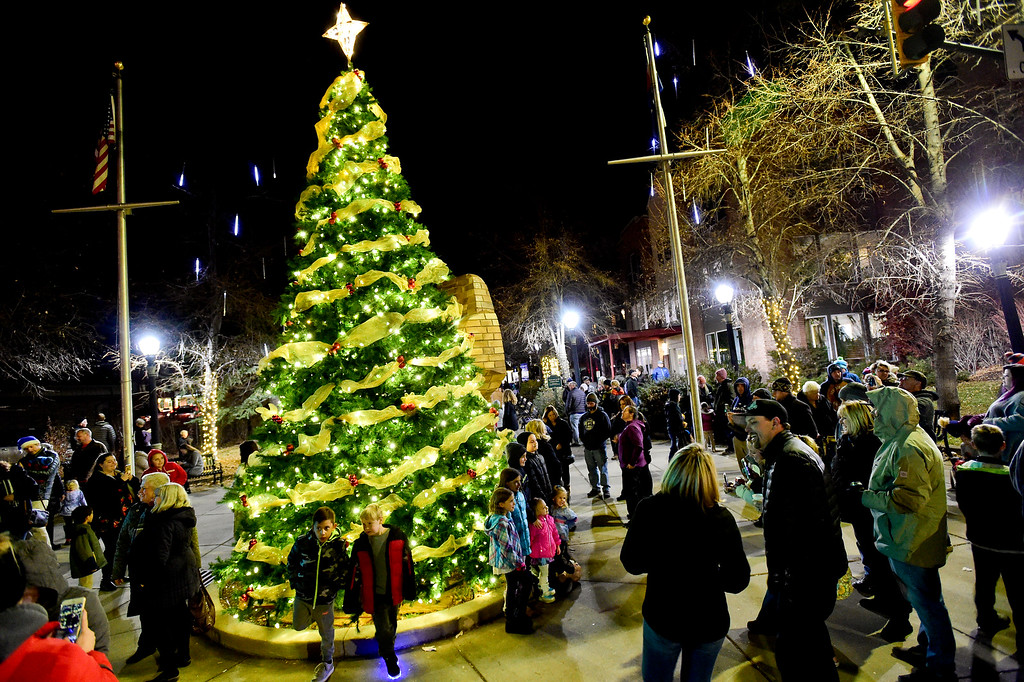 . LONGMONT, CO - NOVEMBER 23:Residents and visitors crowd around the tree to take photos after it was lit for the season at the 6th Avenue Plaza in Longmont on Nov. 23, 2018. This year the tree lighting ceremony features LMNO Puppets, caroling, crafts, food, goodie bags and an appearance by Santa. (Photo by Matthew Jonas/Staff Photographer)