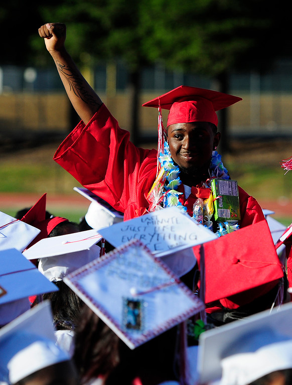 . VALLEJO, CA - JUNE 7, A graduate holds his fist in the air as the choir sings \'Rise Up\' during the Vallejo High School graduation on Thursday. (CHRIS RILEY/TIMES-HERALD)