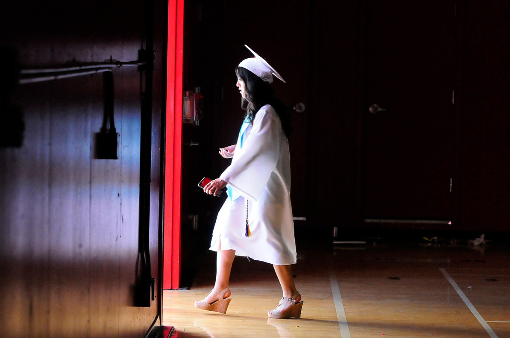 . VALLEJO, CA - JUNE 7, A graduate walks out of Bottari Gym to get some air before the Vallejo High School graduation on Thursday. (CHRIS RILEY/TIMES-HERALD)