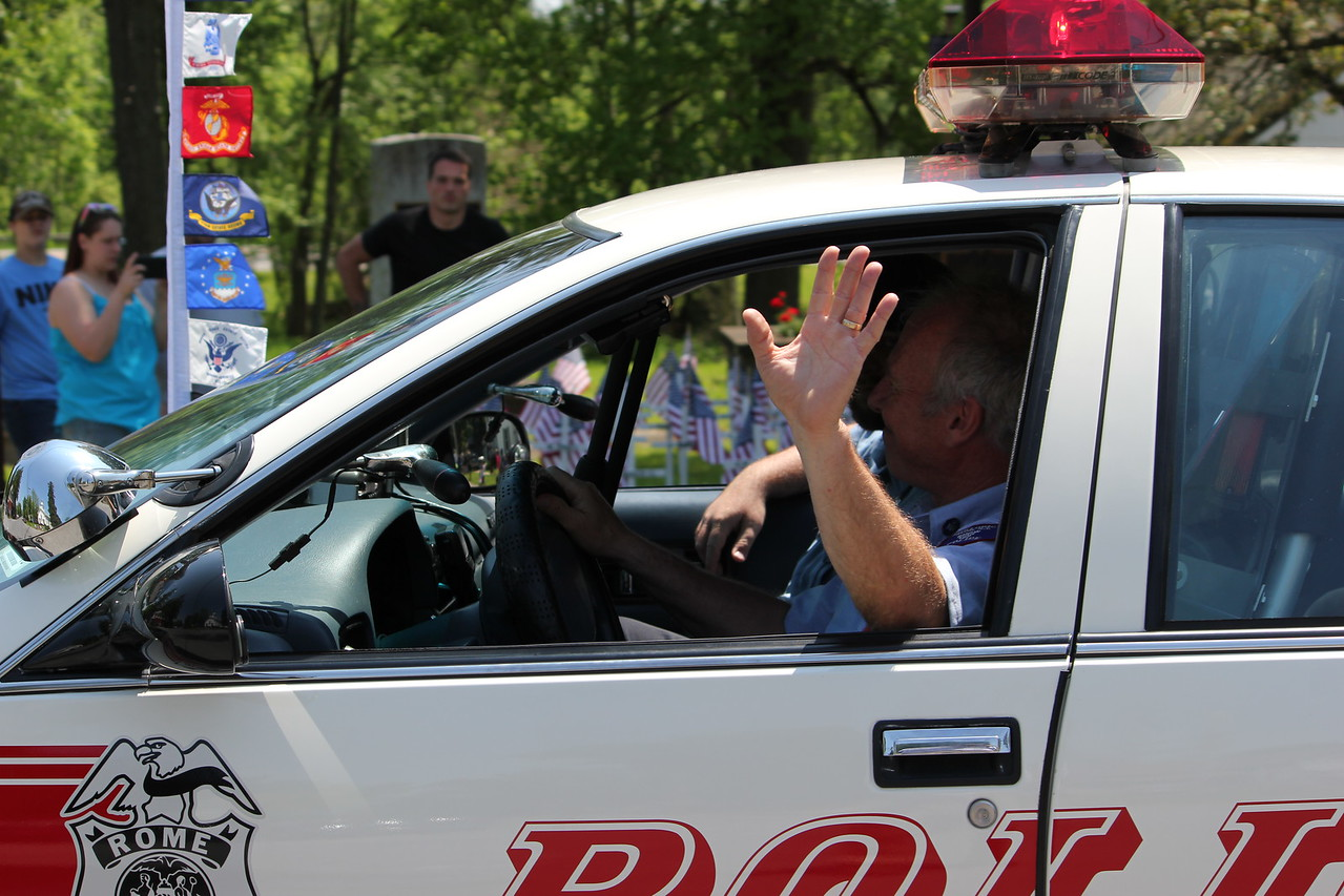 Charles Pritchard - Oneida Daily Dispatch Officers of the Rome Police Department wave to passers at Verona's Memorial Day parade on Monday, May 28, 2018.