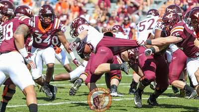 RB Coleman Fox is grabbed from behind by Jarrod Hewitt. (Mark Umansky/TheKeyPlay.com)