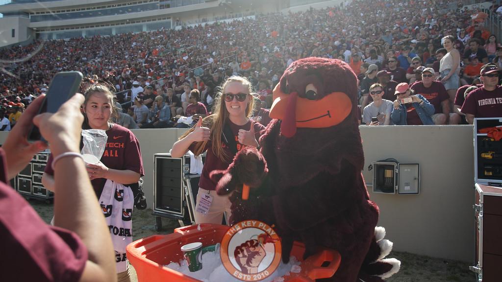 The Hokiebird helps student assistants chop up ice behind the benches. (Mark Umansky/TheKeyPlay.com)