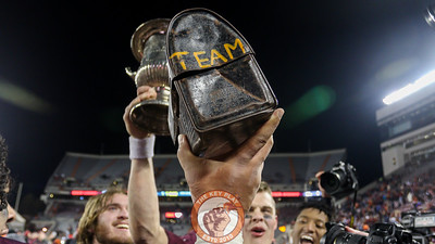 The Hokies hold up the Lunchpail alongside the Commonwealth Cup on the field. (Mark Umansky/TheKeyPlay.com)