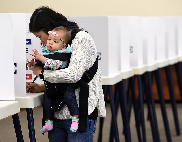 Tracy Fuller of Loveland holds her baby, Kennedy Fuller, 8 months, as she fills out her ballot Tuesday, Nov. 6, 2018, at the vote center in the Loveland Police and Courts Building.   (Photo by Jenny Sparks/Loveland Reporter-Herald)