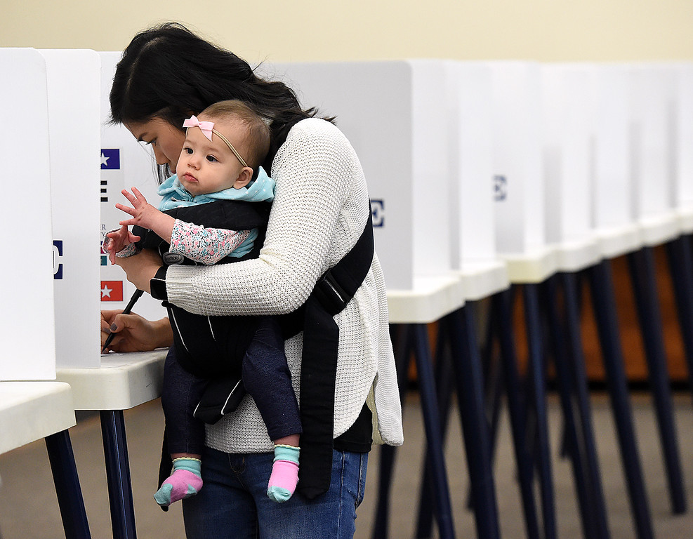 . Tracy Fuller of Loveland holds her baby, Kennedy Fuller, 8 months, as she fills out her ballot Tuesday, Nov. 6, 2018, at the vote center in the Loveland Police and Courts Building.   (Photo by Jenny Sparks/Loveland Reporter-Herald)