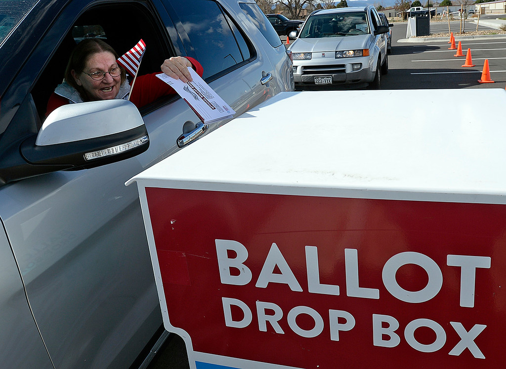 . Linda Yackey of Loveland holds a little American flag as she drops her ballot in the drive-up drop box Tuesday, Nov. 6, 2018, at the Larimer County Loveland Campus building in east Loveland.   (Photo by Jenny Sparks/Loveland Reporter-Herald)