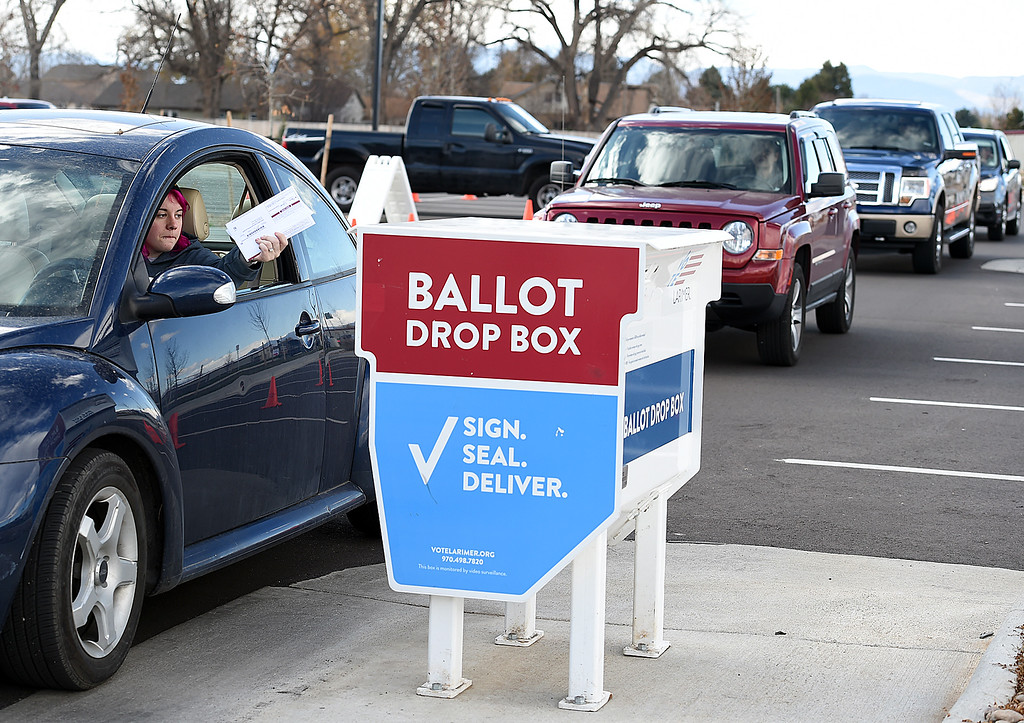 . Drivers wait in line to drop off their ballots in the drive-up drop box as Andy Anderson, left, drops her ballot in Tuesday, Nov. 6, 2018, at the Larimer County Loveland Campus building in east Loveland.   (Photo by Jenny Sparks/Loveland Reporter-Herald)
