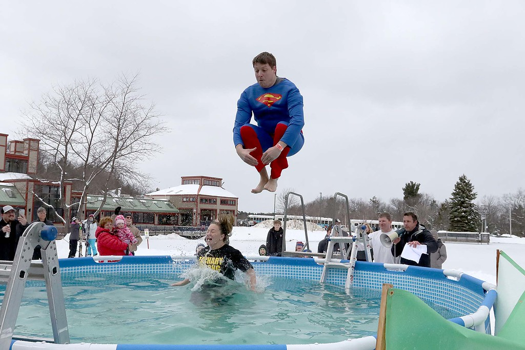 . Anthony Callahan, aka Superman, and his wife Erica Callahan from Ashburnham leap into the freezing cold water during the 2018 Wachusett Polor Dip to raise money for Camp Sunshine at Wachusett Mountain Ski Area in Princeton on Saturday, March 10, 2018. The event raised over $50,000 dollars for the camp. SENTINEL & ENTERPRISE/JOHN LOVE