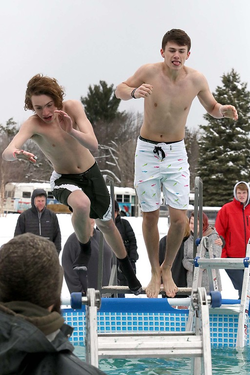 . Gabe Sennott and Lance Jarosz from Harvard leap into the freezing cold water during the 2018 Wachusett Polor Dip to raise money for Camp Sunshine at Wachusett Mountain Ski Area in Princeton on Saturday, March 10, 2018. The event raised over $50,000 dollars for the camp. SENTINEL & ENTERPRISE/JOHN LOVE