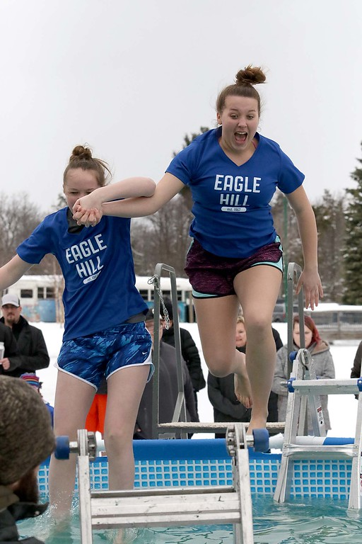 . A couple of participents leap into the freezing cold water during the 2018 Wachusett Polor Dip to raise money for Camp Sunshine at Wachusett Mountain Ski Area in Princeton on Saturday, March 10, 2018. The event raised over $50,000 dollars for the camp. SENTINEL & ENTERPRISE/JOHN LOVE