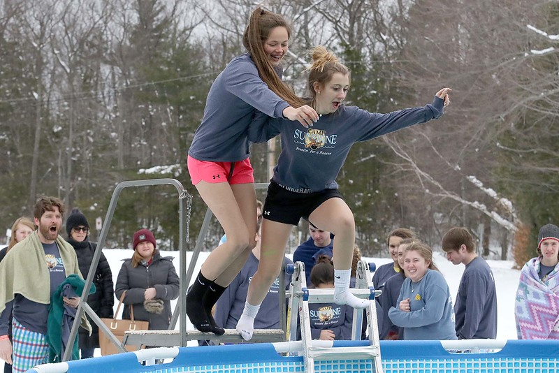 A couple of participents leap into the freezing cold water during the 2018 Wachusett Polor Dip to raise money for Camp Sunshine at Wachusett Mountain Ski Area in Princeton on Saturday, March 10, 2018. The event raised over $50,000 dollars for the camp. SENTINEL & ENTERPRISE/JOHN LOVE