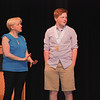 Youth volunteer Finn Tarbox assist actors on stage