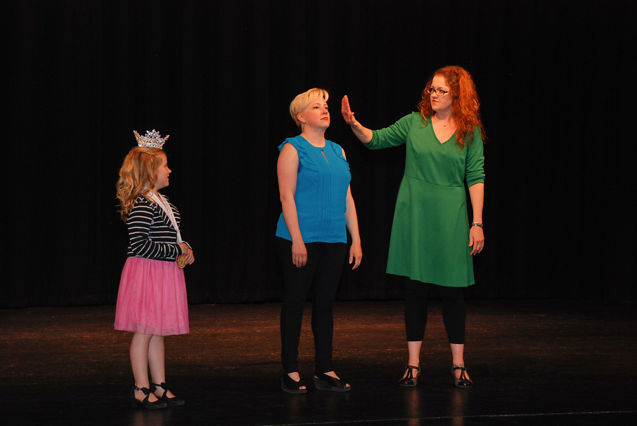 Young volunteer Peyton Rollins assists the actors, Jen and Amy, on stage