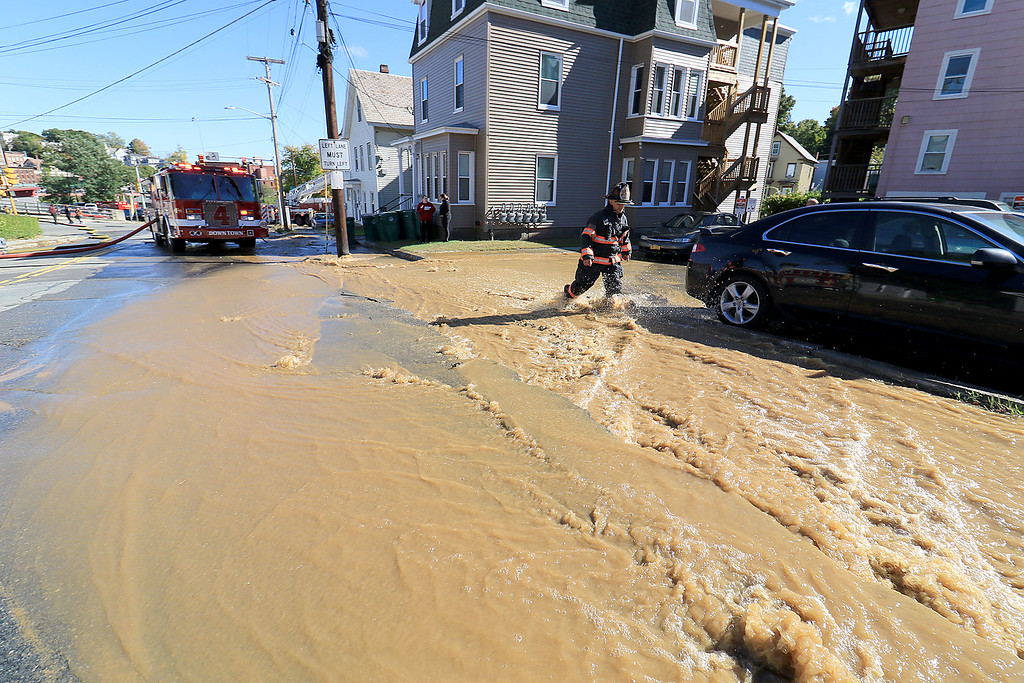 . As the Fitchburg Fire Department battled a fire at 114 and 116 Laurel Street a water main broke and water started rushing down the street. A firefighter walks through the water that was rushing down the street. SENTINEL & ENTERPRISE/JOHN LOVE