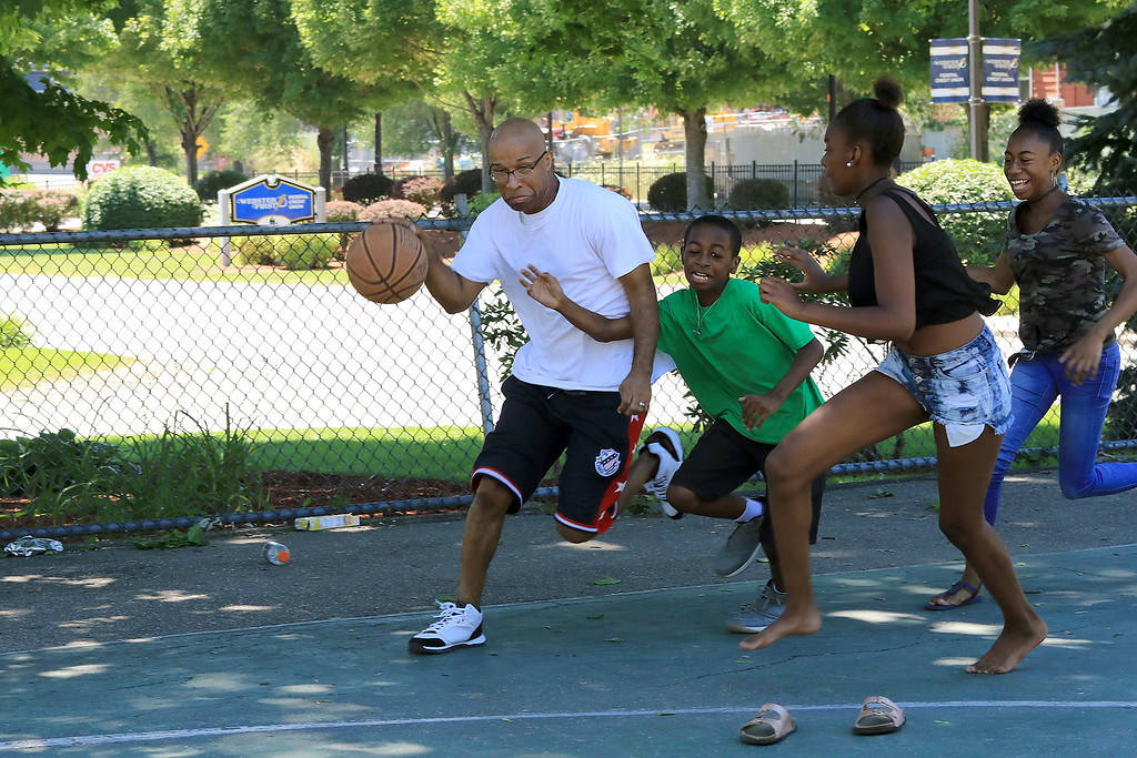 . Christopher Andrade tries to get to the basket while being covered by his son Jacob Andrade, 11, his daughter Alexes, Andrade, 12 in jeans, and his granddaughter Leiyana Taylor, 11 in shorts, as they play some basketball at the Green Street Park in Fitchburg on Friday afternoon. SENTINEL & ENTERPRISE/JOHN LOVE