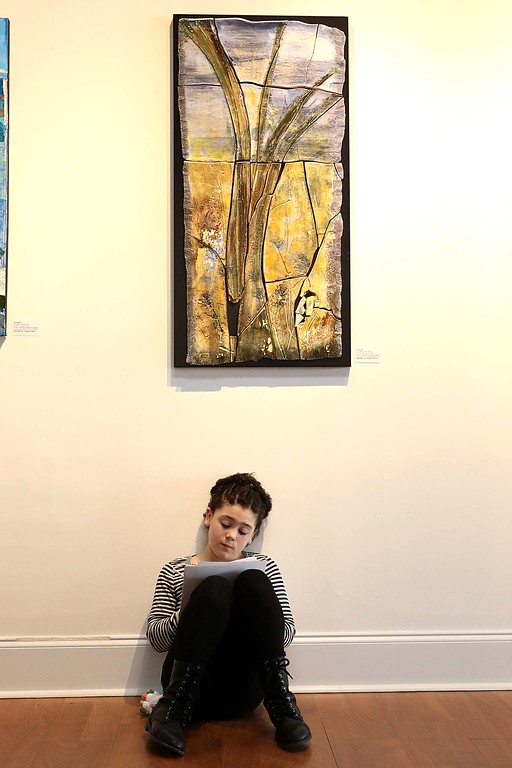 ". Gallery Sitka had the opening for their show ""Love Letters Written in Stone\"" on Saturday, April 7th. It will run for two months. Lillianna Secino, 9, from Fitchburg sit on the floor at the show writing in her journal. SENTINEL & ENTERPRISE/JOHN LOVE"