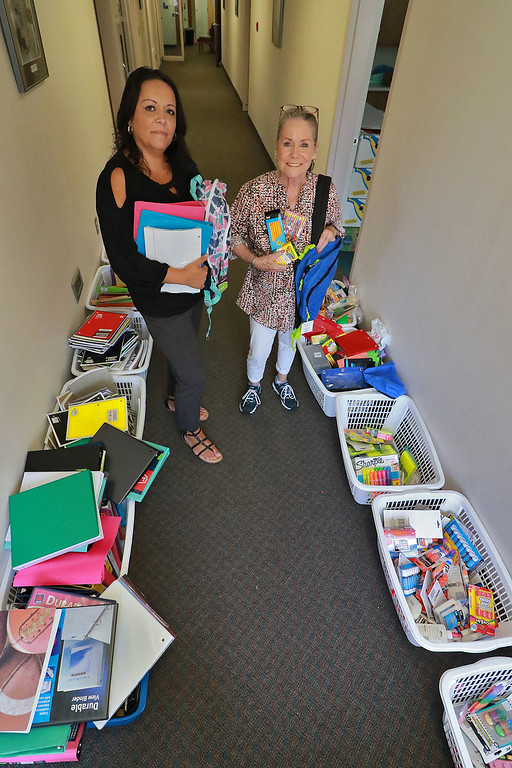 . Maritza Cedeno, on left, the area administrator and Francine Benda the clothing coordinator, both, with Catholic Charities of Worcester County are getting ready to distribute school backpacks and supplies for children in need this school year.  SENTINEL & ENTERPRISE/JOHN LOVE
