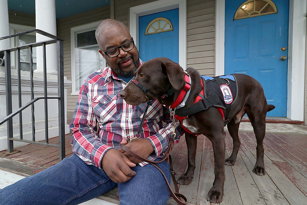 . Veteran Reggie Smith with his service dog Triton a chocolate lab who was a rescue at his home in Fitchburg on Saturday. SENTINEL & ENTERPRISE/JOHN LOVE