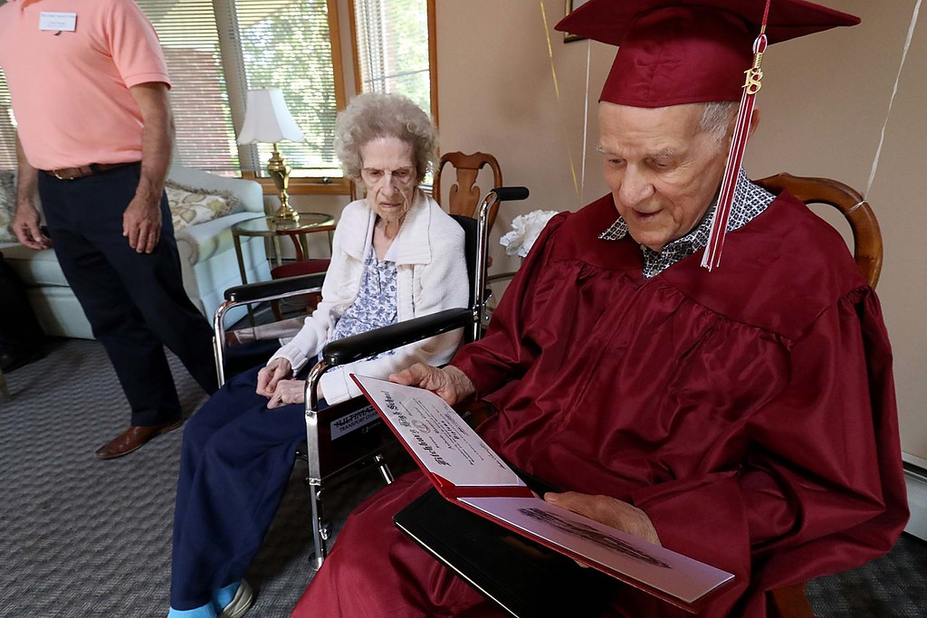 . WWII veteran Andrew Chabot never got his Fitchburg High School diploma in 1939. on Wednesday afternoon while dressed in a cap and gown and sitting next to his wife Katherine Chabot at The Gables of Fitchburg he final got it from Fitchburg High School Principal Jeremy Roche.  Chabot and his wife Katherine look over his diploma. SENTINEL & ENTERPRISE/JOHN LOVE