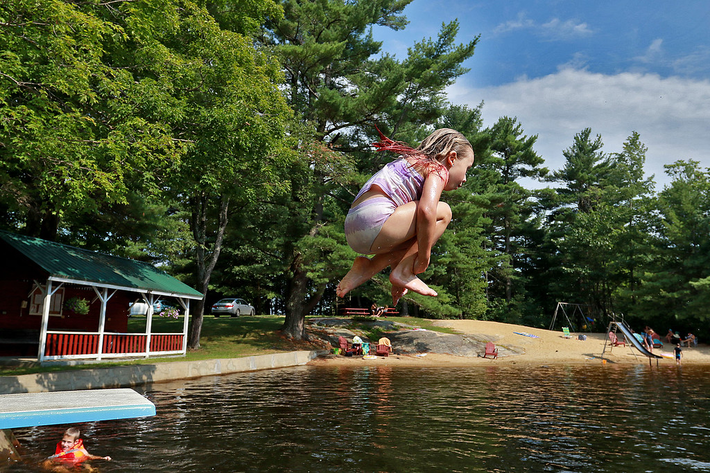 . It was in the 90\'s on Tuesday across the North Central Ma region. To stay cool in Ashburnham some took to swimming in Naukeag Lake on Packard Hill Road. Leaping into the lake off the diving board to do a cannonball is Ruth Normandin, 6, of Ashburnham. SENTINEL& ENTERPRISE/JOHN LOVE