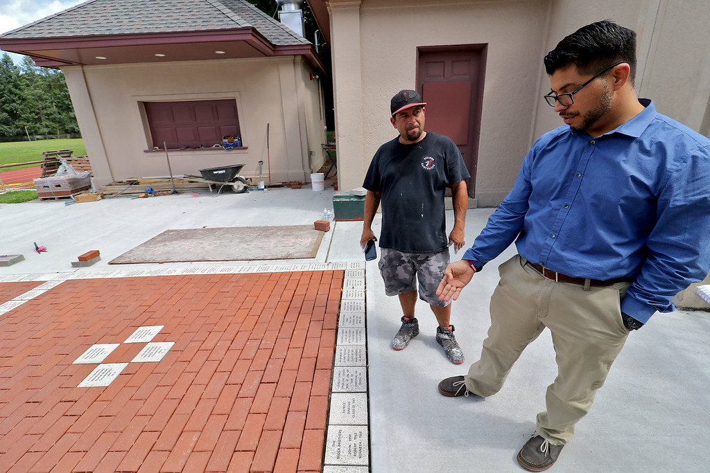 . Crocker Field entrance has been getting an up grade this summer. They are putting in some bricks that people have bought around the Red Raider symbol. Luis Alvarado Ctrocker Fields grounds keeper and Josue Gonzalez, blue shirt, the Districts building maintenance manager talk about all the work being down to the 100 year old field.    SENTINEL & ENTERPRISE/JOHN LOVE