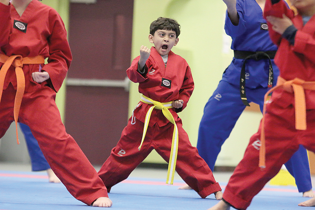 . Practicing some poses at the new Taekwondo studio in Fitchburg on Wednesday night is yellow belt J. Rodriquez, 6, from Fitchburg. SENTINEL & ENTERPRISE/JOHN LOVE