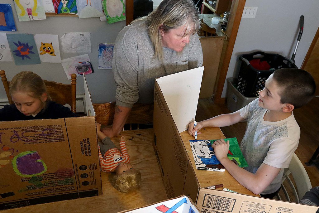 . Mary Sirois, center, works with her adopted children, from right, Christian Siriois, 11, and Grace Sirois, 9, during project time at their house in Leominster just before packing them up to go camping for the weekend on Friday afternoon. both started out as one of her over 200 foster kid. SENTINEL & ENTERPRISE/JOHN LOVE