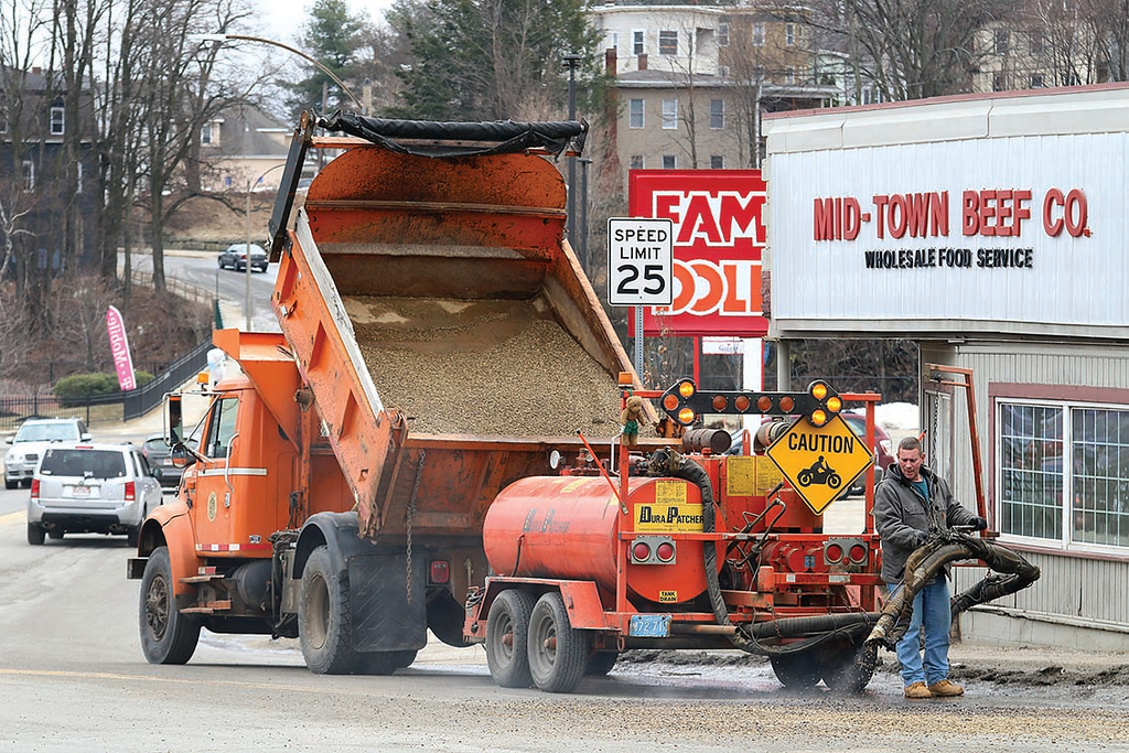. A Fitchburg Department of Public Works employee fills in some potholes on Water Street Thursday afternoon. SENTINEL & ENTERPRISE/JOHN LOVE