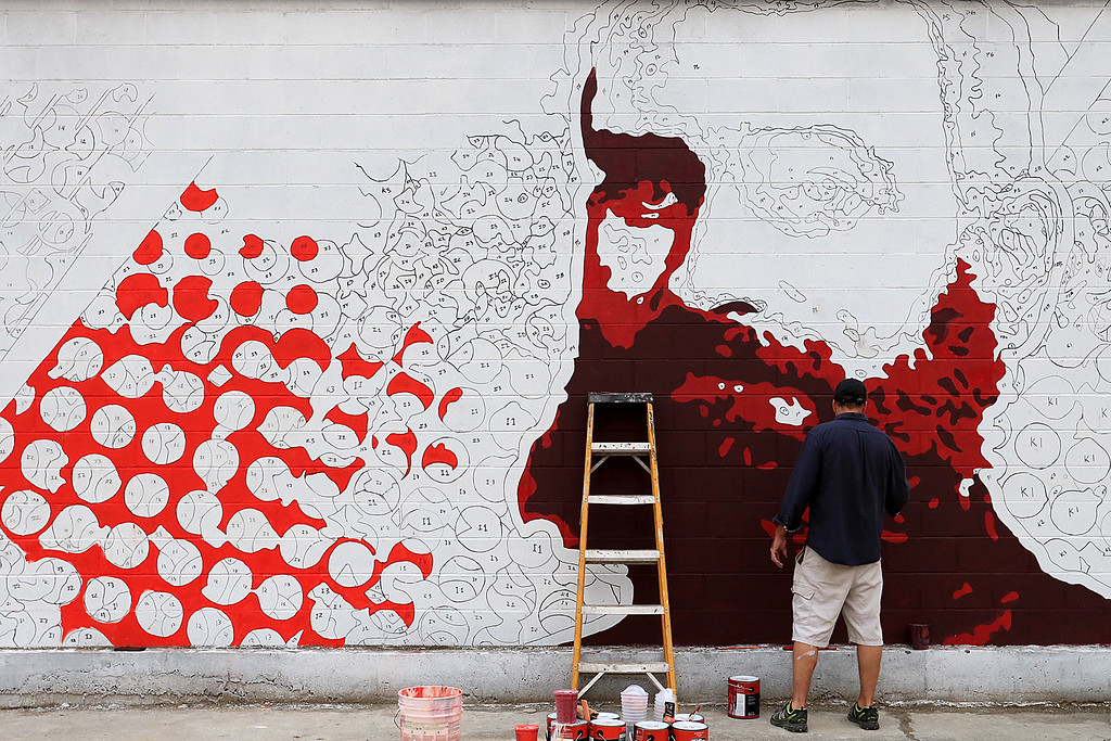 . EXCHANGE -Fitchburg resident and artist Jon Allen works on a new Iver Johnson themed mural on Main Street on Wednesday night. SENTINEL & ENTERPRISE/JOHN LOVE