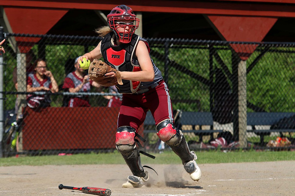 . Fitchburg High School softball catcher Audrey Johnson picks up a bunt in front of the plate and gets ready to throw to first for an out during their game against Leominster High School. SENTINEL & ENTERPRISE/JOHN LOVE