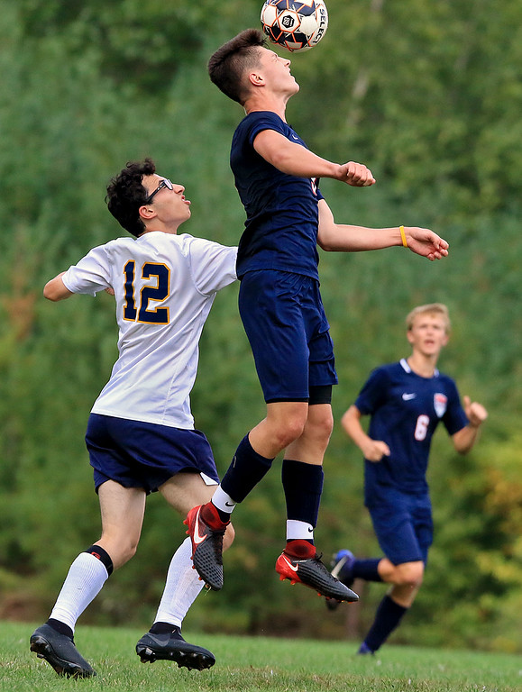 . Littleton High School boys soccer traveled to Townsend on Thursday afternoon to play North Middlesex Regional High School. NMRHS\'s Jacob Talmer heads the ball as he jumps over LHS\'s Anthony Rawa during action in the game. SENTINEL & ENTERPRISE/JOHN LOVE