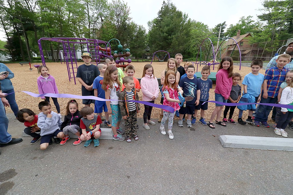 . Kids enjoy playing on the new equipment at Wallis Park Playground in Lunenburg during the ribbon cutting on Tuesday morning. Kids stand next to Thersea Letarte, 7, as she cuts the ribbon to official open the park at the small ceremony. SENTINEL & ENTERPRISE/JOHN LOVE