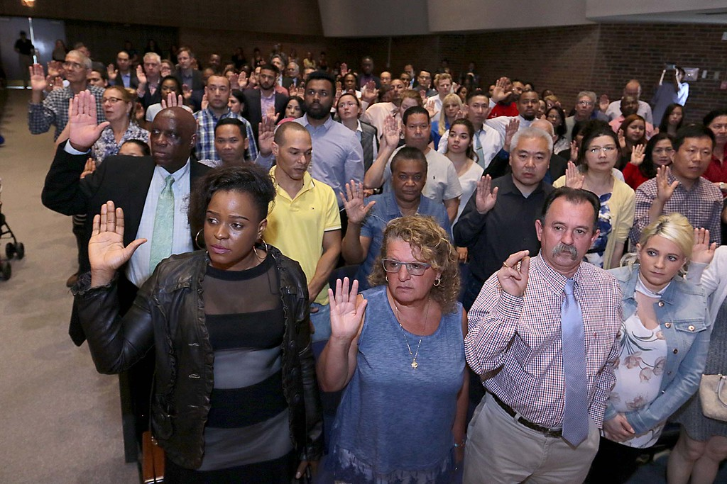 . Many swear in to become new United States citizens during the naturalization ceremony held at the Weston Auditorium at Fitchburg State University Friday, May 4, 2018. SENTINEL & ENTERPRISE/JOHN LOVE