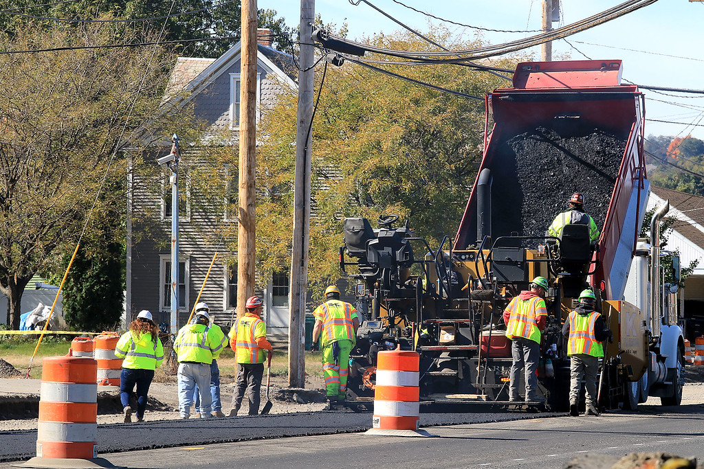 . A dump truck pours some asphalt into a paver as they work on Summer Street on the Fitchburg and Lunenburg line on Thursday morning, October 19, 2018. SENTINEL & ENTERPRISE/JOHN LOVE