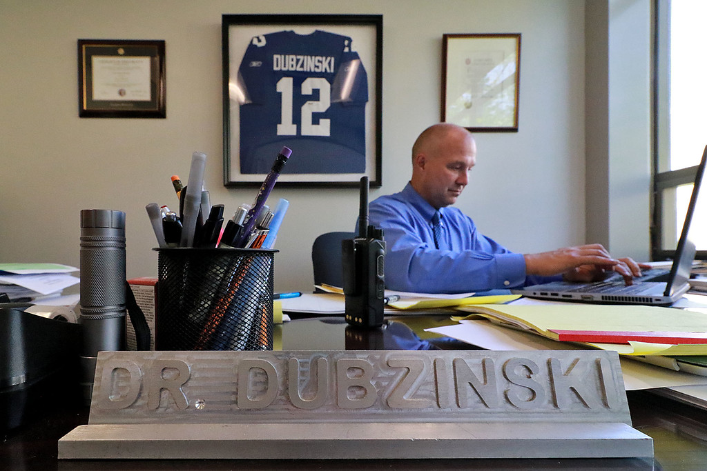 . Leominster High Schools new Principal Steve Dubzinski was working on Tuesday, along with the schools teachers and faculty, to get everything ready for opening day on Wednesday. Dubzinski looks over some paper work in his office with his grandfathers jersey on the wall behind him. His grandfather and his father were also principals.  SENTINEL & ENTERPRISE/JOHN LOVE