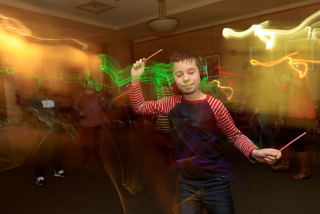 . The Leominster Public Library hosted a 90\'s Disco dance where everyone wears wireless headphones and dance to songs being simultaneously broadcast to all of them. Luke Iannucci of Sterling enjoys dancing around during the event on Tuesday night, November 21, 2018. SENTINEL & ENTERPRISE/JOHN LOVE