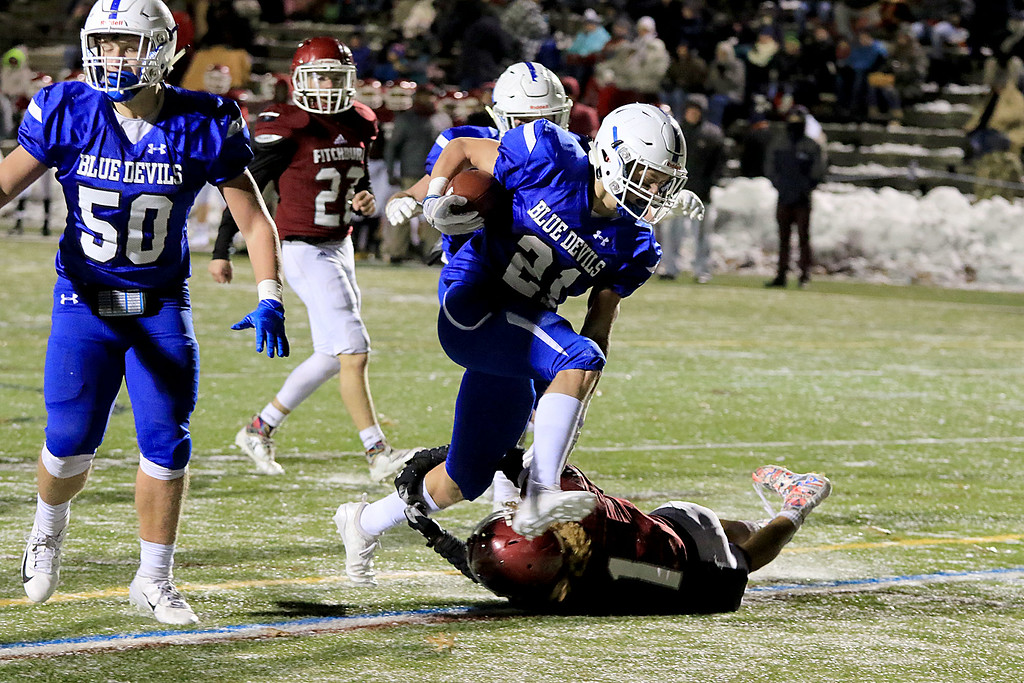 . The Thanksgiving day game with Leominster High School vs Fitchburg High School was played at  Doyle Field in Leomiinster on Wednesday night, November 21, 2018. LHS\'s Adam Couch goes over FHS\'s Trey Winters for a touchdown. SENTINEL & ENTERPRISE/JOHN LOVE
