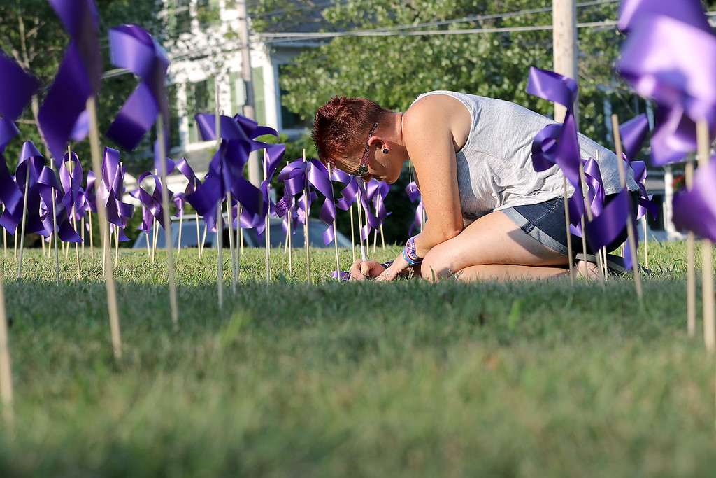 . On the Lawn of the Congrational Church in Gardner was just over 1900 purple ribbons to symbolize home many people lost their lives to addiction in 2017. Tina DuBois writes a note to someone she lost to addiction on one of the ribbons. SENTINEL & ENTERPRISE/JOHN LOVE