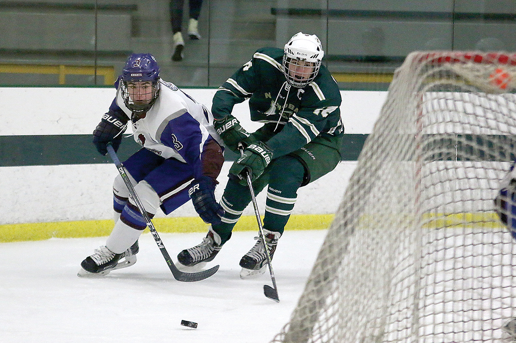. Lunenburg/Ayer Shirley player Declan Fitzpatrick and Nashoba Regional High School player Harrison Cartergo after a loose puck behind the net during action in the game. SENTINEL & ENTERPRISE/JOHN LOVE