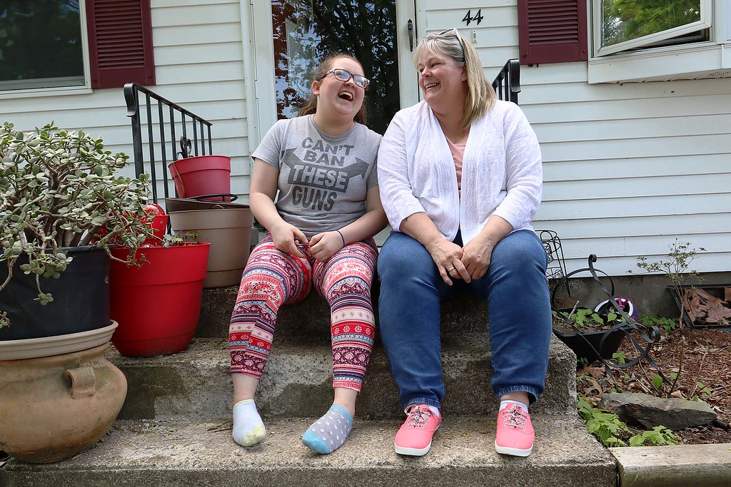 . Mary Sirois, on right, has a good laugh with her adopted child Lauren Sirois, 17, who started out as one of her over 200 foster kids, at their home in Leominster on Wednesday afternoon. SENTINEL & ENTERPRISE/JOHN LOVE