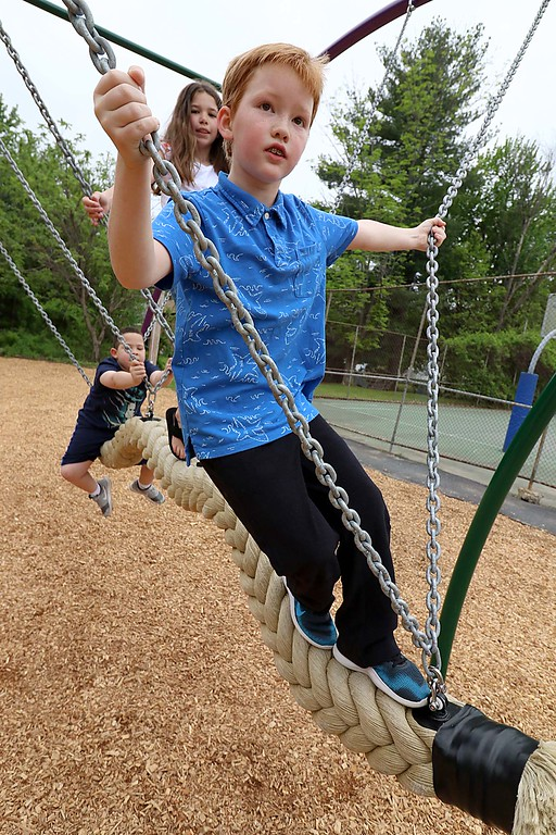 . Kids enjoy playing on the new equipment at Wallis Park Playground in Lunenburg during the ribbon cutting on Tuesday morning. Having fun on this unique rope swing is, l-r, Maddox Hall, 7, marie Adams, 10, and Waylon Letartee, 10. SENTINEL & ENTERPRISE/JOHN LOVE