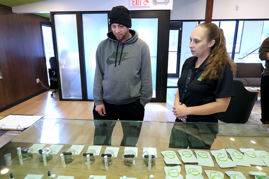 . A soft opening was held for the area\'s first pot dispensary Sanctuary Medicinals in Gardner, which is going to expand into recreational sales next month. Brett Johnson, 32, who lives in Gardner and grew up in Leominster works with Patient Care Advisor Koral Brooks as he picks out what he needed. He was the first customer in the dispensary on it\'s opening day, November 23, 2018. SENTINEL & ENTERPRISE/JOHN LOVE