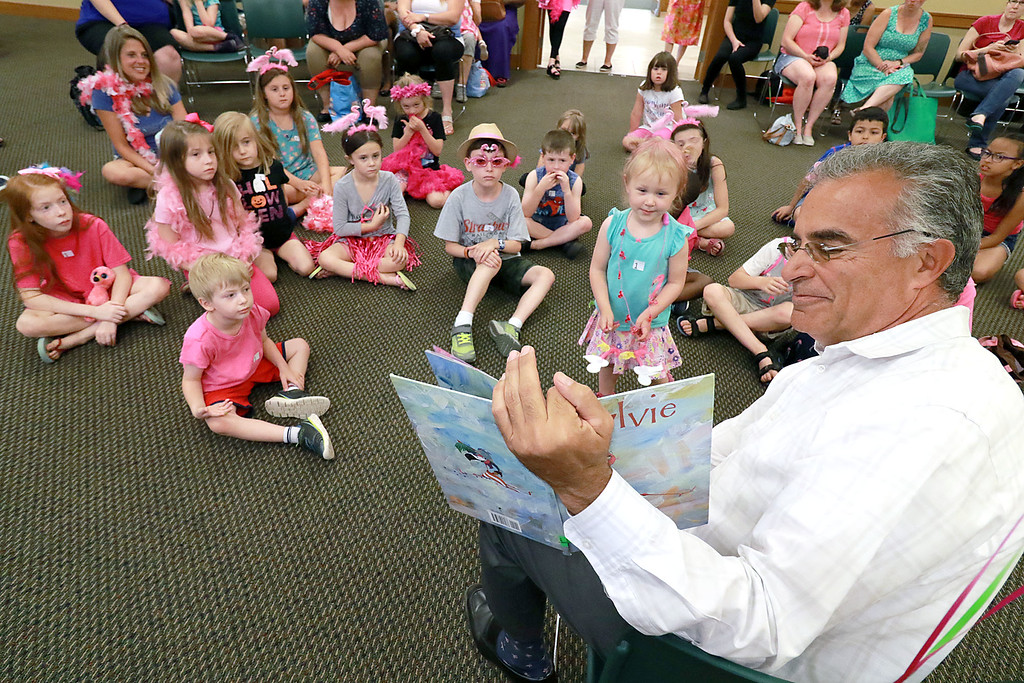 . Leominster Mayor Dean Mazzarella read the book Sylvie by Jennifer Sattler to the children during the celebration of National Pink Flamingo Day at the Public Library on Friday afternoon. SENTINEL & ENTERPRISE/JOHN LOVE