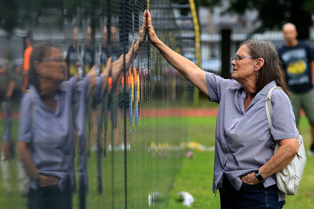 ". Many came out to see ""The Wall that Heals\"" at Crocker Field in Fitchburg on Saturday afternoon. Pauline Sommala reflects on her good friend and classmate of Fitchburg High School class of 1965 as she touches his name on the wall. SENTINEL & ENTERPRISE/JOHN LOVE"